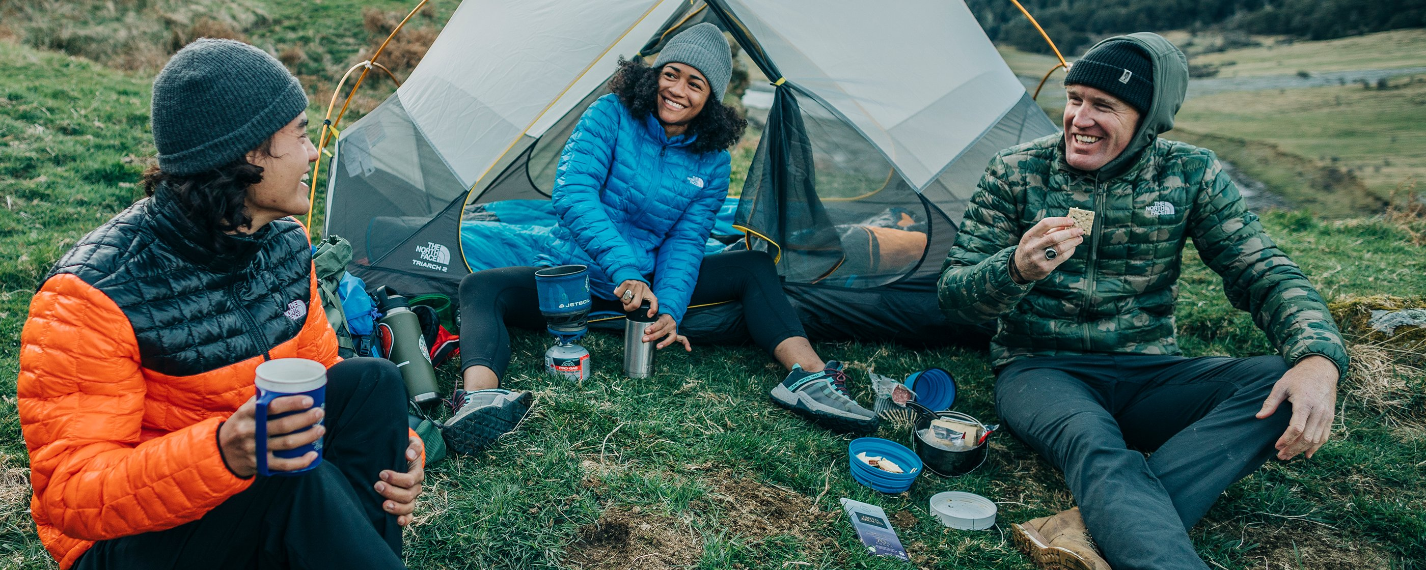 A group of people camping outdoors sit on the ground, enjoying snacks and coffee together.