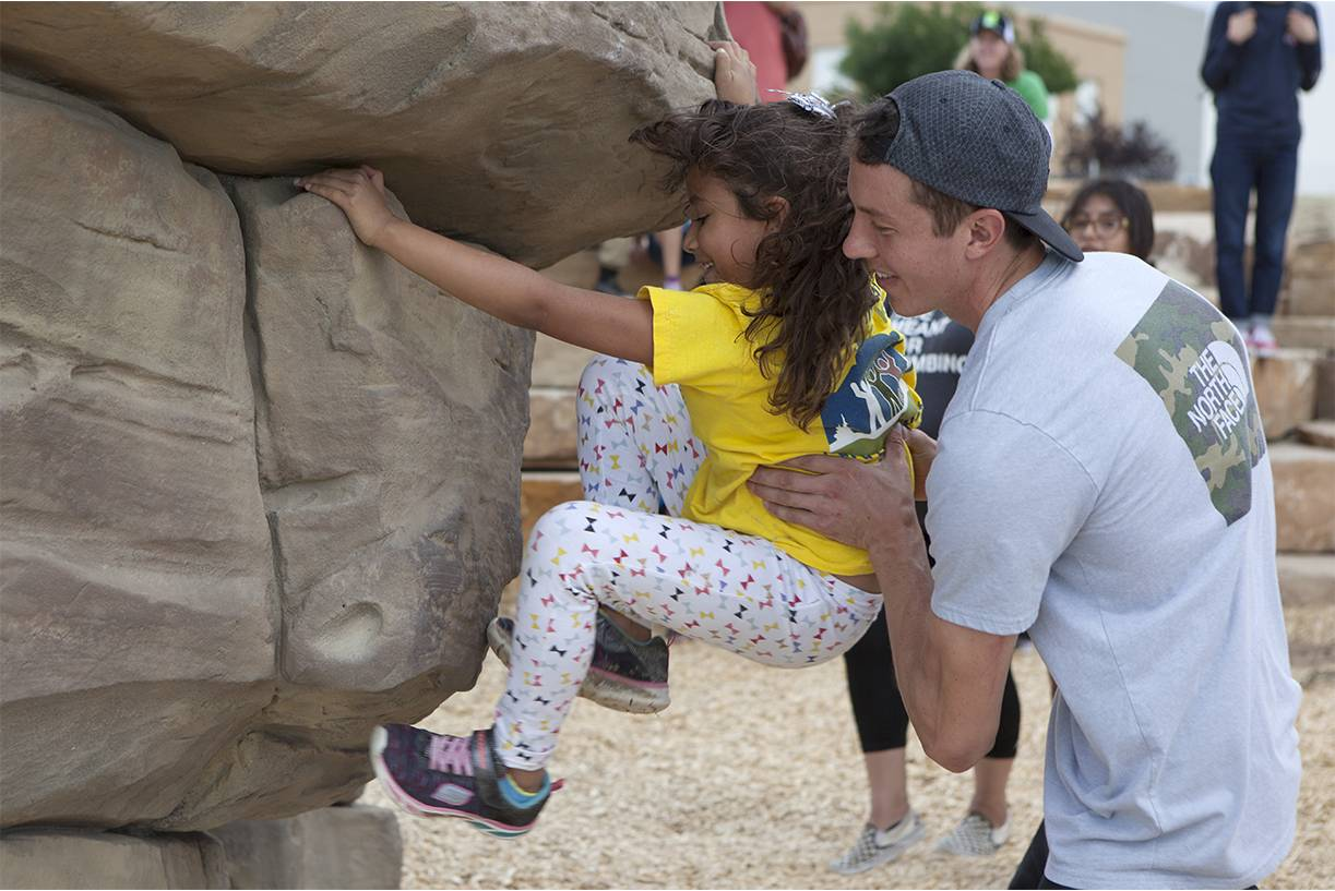 North Face employee holds little girl as she climbs on fabricated bouldering wall in Downtown Denver Colorado at Montbello open space