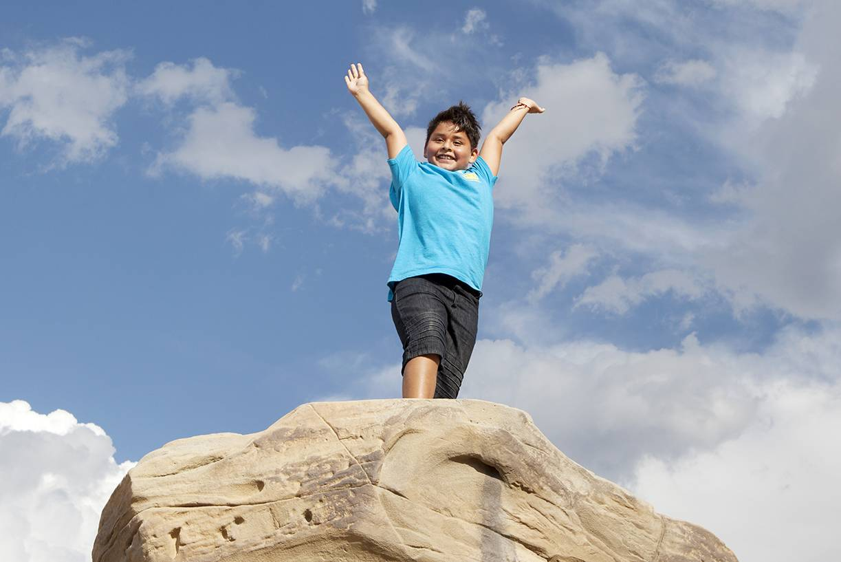 Kid stands on top of North Face Bouldering wall in Montbello open space in Denver Colorado